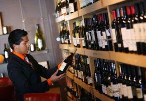 Beverage director Jordan Nova selects a bottle from the many featured wines at 1313 Main in Napa on Friday, October 11, 2013. (Conner Jay/The Press Democrat)