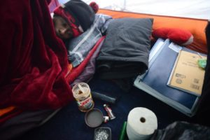 Gerri Jackson, 22, going back to bed next to his school books after scraping the bottom of a Skippy peanut butter and chocolate jar for his breakfast on a cold early Sunday morning in his tent in a wooded area of a Santa Rosa park. November 24, 2013. (Photo: Erik Castro/for The Press Democrat)