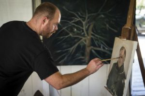 Artist in residence Frank Ryan painting a portrait of Rodger Warnecke at Chalk Hill studio. (photo by Chris Hardy)