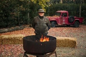 Rodger Warnecke warms himself by the fire at a barbecue at the ranch.  (photo by Chris Hardy)