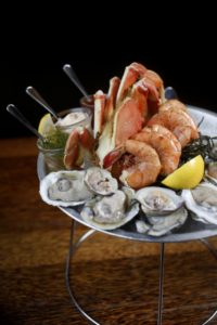 The medium seafood platter with peel and eat Gulf prawns, Blue Point oysters, littleneck clams, and half a Dungeness crab with a variety of dipping sauces at Willi's Seafood and Raw Bar in Healdsburg. (photo by Beth Schlanker)