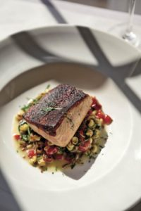 Chef Andrew Truong's blackened salmon is served atop a medley of roasted summer vegetables and farro at Terrapin Creek in Bodega Bay.
