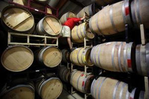 Hardy Wallace with Dirty and Rowdy Family Wines climbs up the tall stacks of barrels at Punchdown Cellars to pull a sample in Santa Rosa on Tuesday, July  15, 2014. (Conner Jay/The Press Democrat)