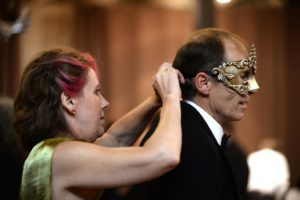 Tracy Laird helps to fasten the mask of Shawn Flores during the 18th annual 4-A-Child Masquerade Ball, a benefit of the California Parenting Institute held Saturday evening at the DeTurk Round Barn in Santa Rosa. November 8, 2014.  (Photo: Erik Castro/for The Press Democrat)
