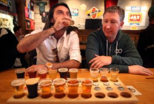 Cristian Jara Villegas, left, and Jay Fellers share a sampler flight of beers at Russian River Brewing Company in Santa Rosa. (photo by Christopher Chung)