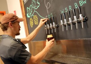 Seth Wood pouring beer at Woodfour Brewing Company in The Barlow in Sebastopol. (photo by Crista Jeremiason)