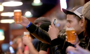 Sebastian Hernandez of Rancho Cucamonga photographs a glass of Pliny the Younger at The Russian River Brewing Co. in Santa Rosa, Friday Feb. 7, 2014. (Kent Porter / Press Democrat)