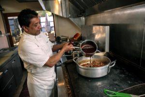 Mateo Granados pours mole sauce on lamb meat that will go into enchiladas.