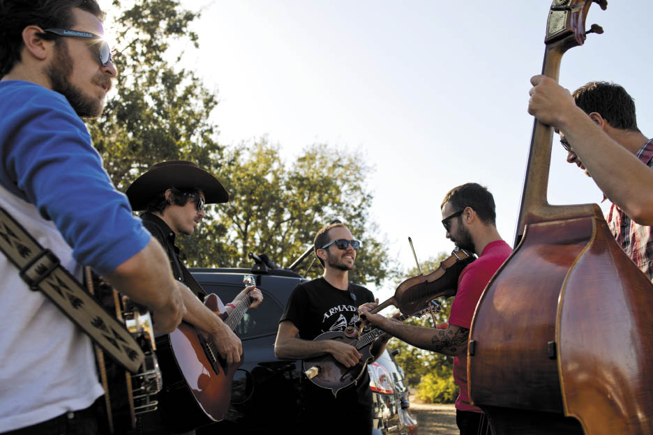 The Brothers Comatose — Alex Morrison, left, Ben Morrison, Ryan Avellone, Josh Rabie and Ryan Lukas — warm up backstage before their performance at the 2014 EarleFest.