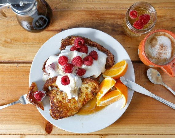 Cinnamon French toast made from Village Bakery brioche topped with butter, fresh whipped cream, organic raspberries and real maple syrup with orange slices, sparkling wine and a cappuccino at Estero Cafe in Valley Ford, California on Wednesday, January 27, 2016. (Alvin Jornada