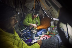 Tommy Caldwell and Kevin Jorgeson free climbing El Capitan's Dawn Wall. Big-wall chef Tommy Caldwell cooks up some gruel on his hanging propane stove in his portaledge camp 1,200 feet up the side of El Capitan. (photo by Corey Rich)