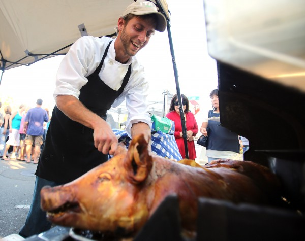 Joe Rueter, chef with the Green Grocer, serves a porchetta during Windsor's Farmers Market on the Town Green, June 14, 2012.