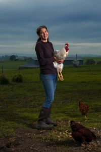 Dawn Dolcini of Tully Dolci Organic Farm holds a Leghorn rooster.