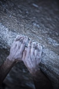 Free climbing El Capitan's Dawn Wall. Kevin Jorgeson curls his fingers on top of a granite edge. (photo by Corey Rich)