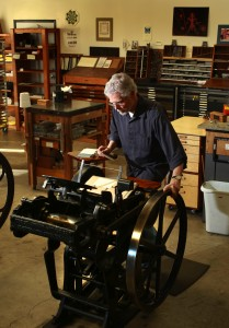 Eric Johnson prints announcements for an upcoming show on an authentic platen press circa 1930 at Iota Press in Sebastopol.