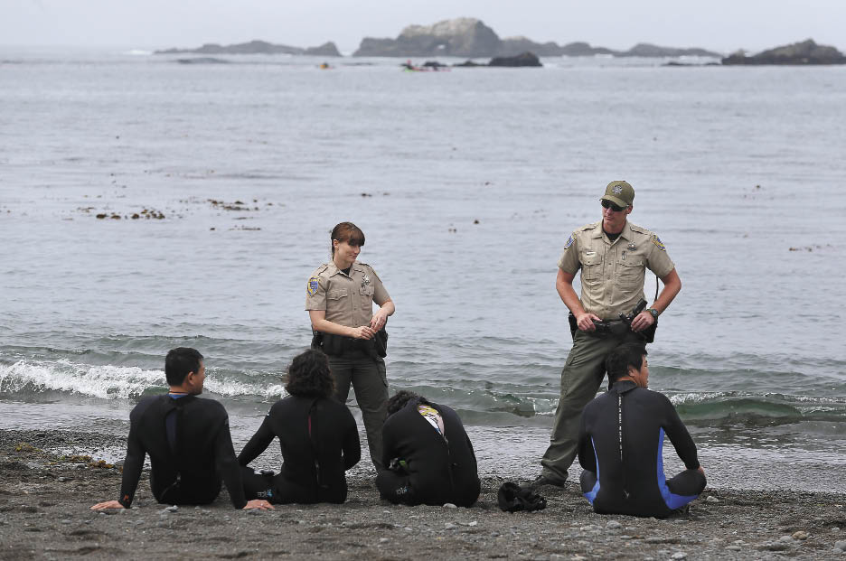 Wardens Kathleen Boele and Todd Kinnard detain divers who were cited for multiple abalone hunting violations at van Damme State Park.