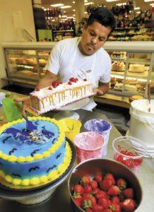 Ruben Altamirano decorates a tres leches cake at Lola's Market in Santa Rosa.