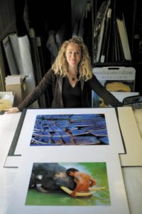 Lisa Kristine, shown with two of her photographs. (photo by Chris Hardy)