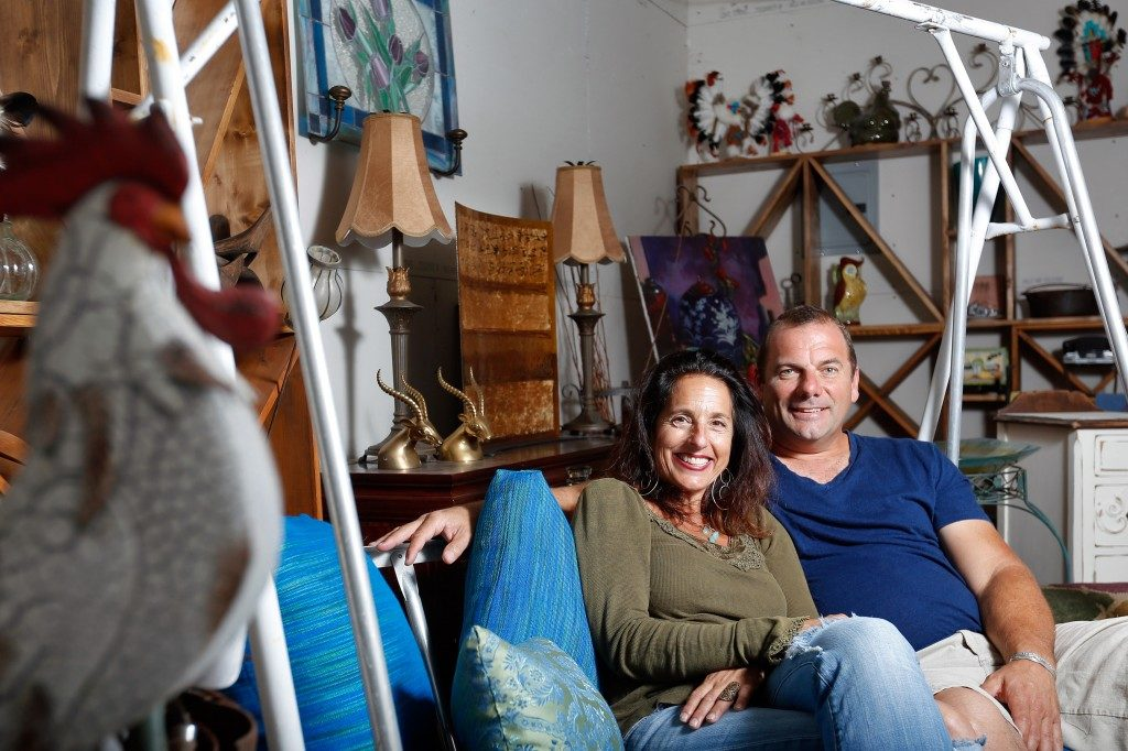 Leslie Boutell and Simon Purshouse, owners of Urban Refind, sit on a porch swing amongst many of their other wares at their shop in Sonoma, California on Thursday, October 15, 2015. (Alvin Jornada / The Press Democrat)