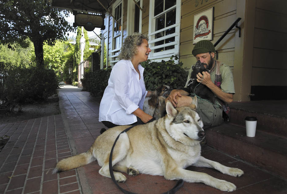 Gail Cohen, with her dogs Dorje and Bandit, stops to talk with Clay Lynch, with his dog Batboy, on the Union Hotel steps.