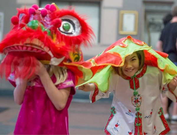 Keelyn Walker, right, peeks from under a lion costume while Brook Szczekocki greets guests arriving for a Chinese New Year celebration at the Veteran's Memorial Building in Santa Rosa on Saturday, Feb. 21, 2015. The Redwood Empire Chinese Association hosted the event honoring the year of the Ram. (Jeremy Portje / For The Press Democrat)
