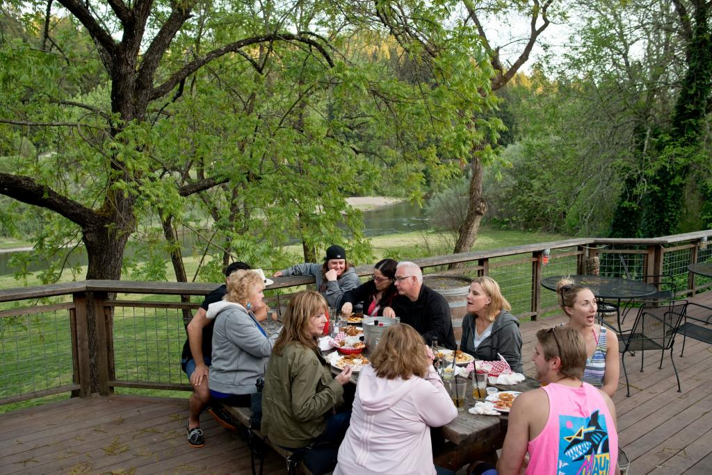"Visitors have dinner in view of the Russian River on the patio of Stumptown Brewery in Guerneville. Don't miss the infamously named ""Donkey Punch"", a refreshing hoppy lager with a kick, and a thick body. (Alvin Jornada / The Press Democrat)"