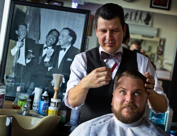 The 50's are back in style at the Santa Rosa Barber Shop. Owner Eric Gardea runs pomade through the hair of Cody Garzini. (JOHN BURGESS / The Press Democrat)