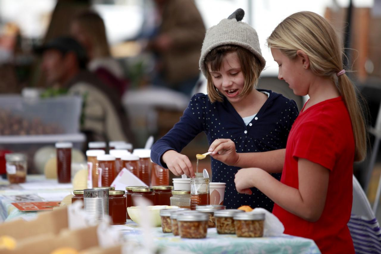 Gwyneth Barker, 7, left, and Amber Vanoni, 8, taste honey from the Beelove Honey during the West End Farmers Market in Santa Rosa. (Beth Schlanker / The Press Democrat)