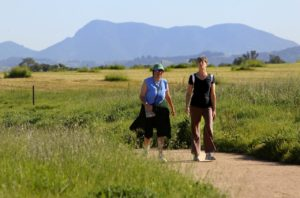 Debra Capri, left, and Chris Sittig take a morning hike along the Laguna de Santa Rosa trial with Mt. St. Helena in the background.   (John Burgess/The Press Democrat)