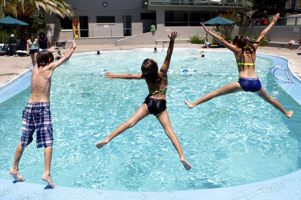 Siblings, Carter Gardea, 9, Sophia, 7, and Camille, 12, jump into the pool at Morton's Warm Springs in Glen Ellen (Beth Schlanker / The Press Democrat)