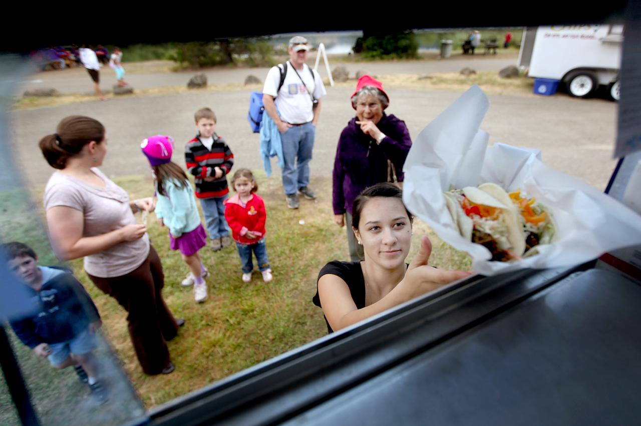 """7/18/2012: B1: PC: Robin Altman of Street Eatz """"Flavors of the World"""" mobile food truck serves up tacos to visitors at Spring Lake, Tuesday July 17, 2012 in Santa Rosa as part of the Spring Lake Regional Park summer picnic gathering involving local food trucks. (Kent Porter / Press Democrat) 2012"""