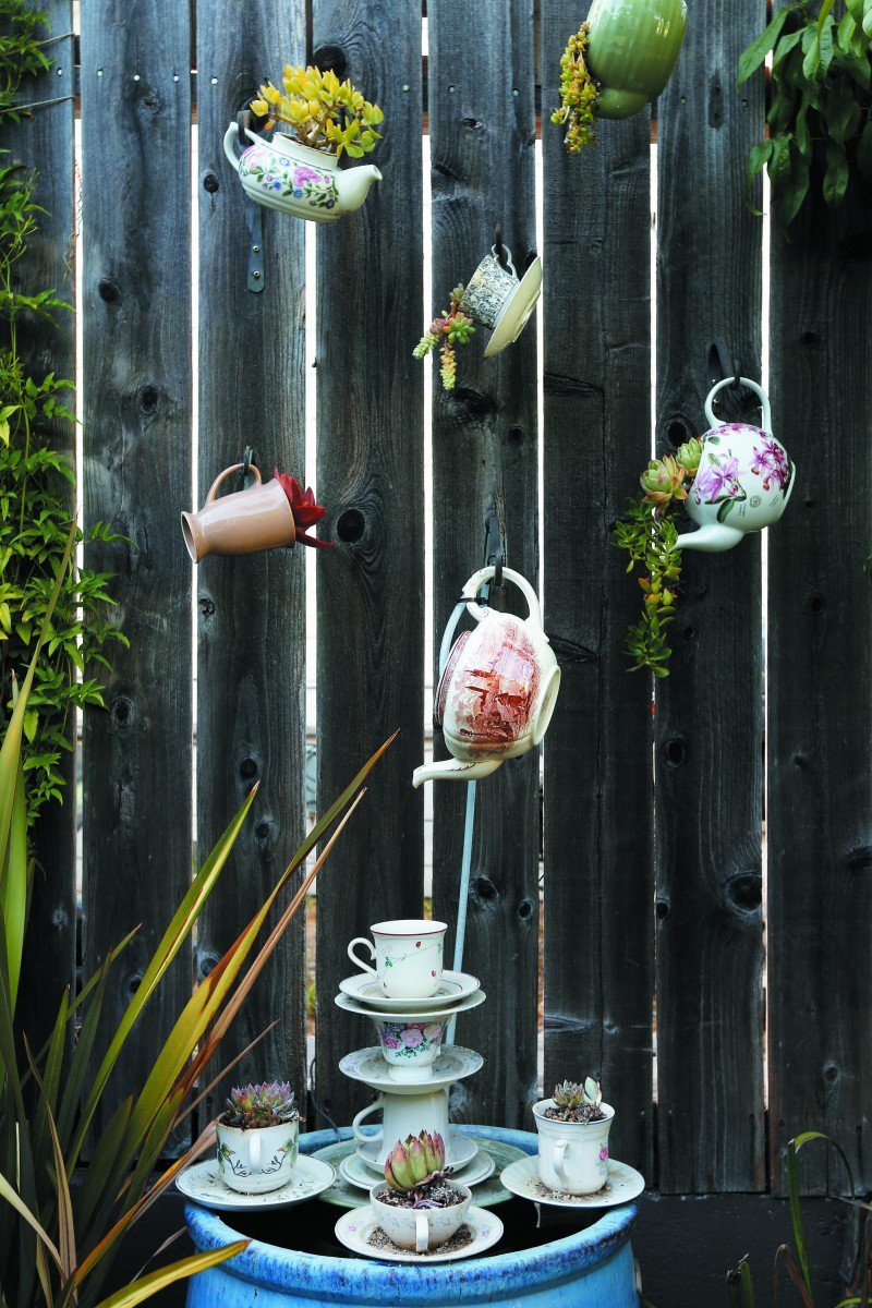 The home's rear courtyard has several whimsical touches: an industrial-size coffee maker from a battleship repurposed as a planter; an old claw-foot bathtub turned into a couch; a fountain made of teapots and cups. (Photography / Alvin Jornada)