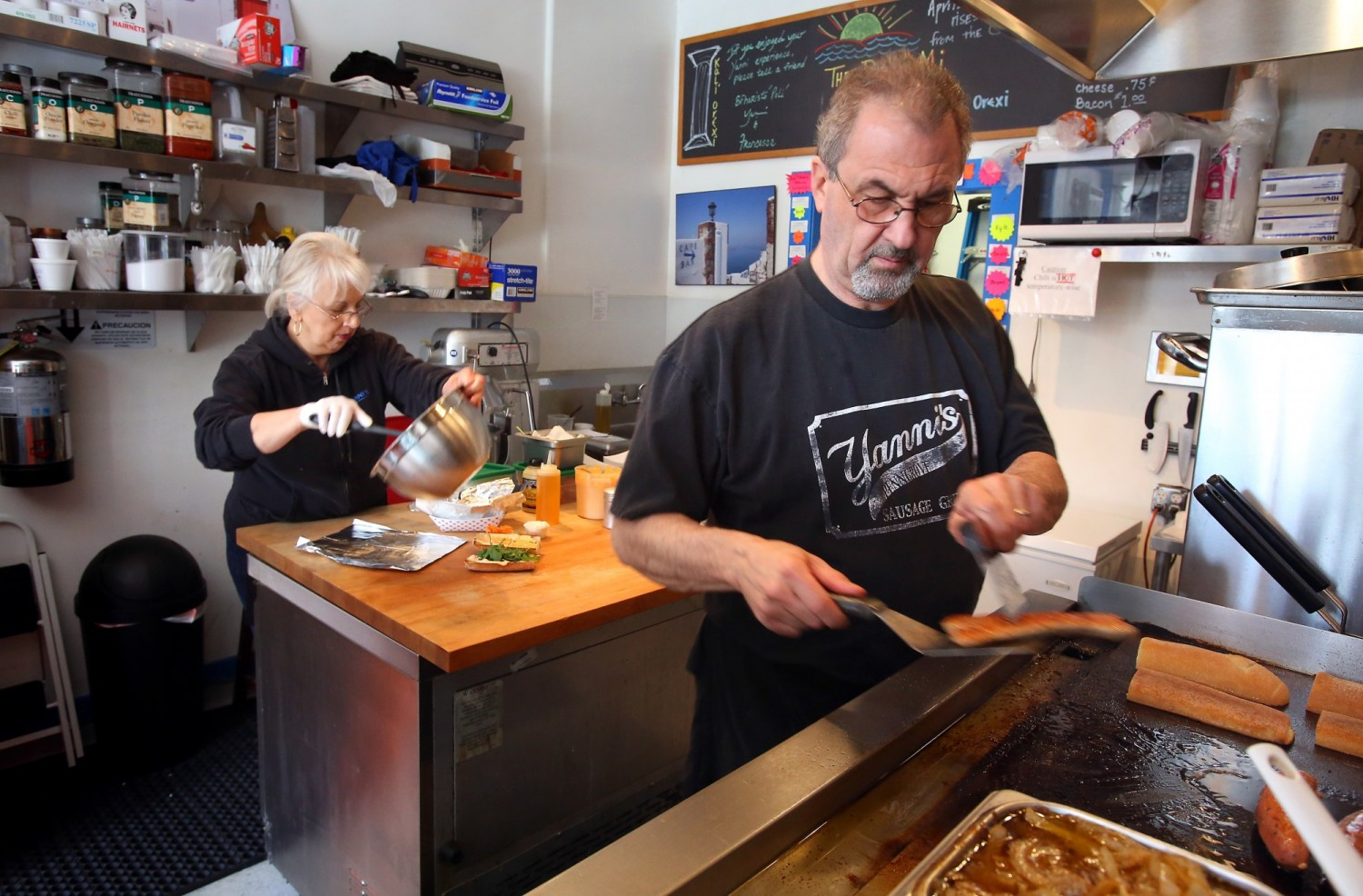 John Vrattos cooks a sausage on the grill as his wife Francesca prepares Greek fries at their Penngrove restaurant, Yanni's Sausage Grill. They have been married for 35 years. (Christopher Chung / The Press Democrat)