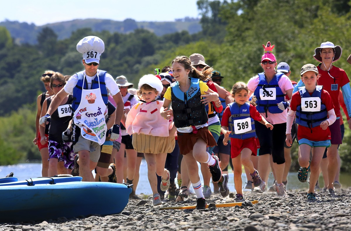 Families race to their kayaks for the start of the double kayak division of The Great Russian River Race at Rio Lindo Beach. (John Burgess / The Press Democrat)