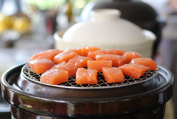 Cooking salmon on a donabe. (Heather Irwin/The Press Democrat)