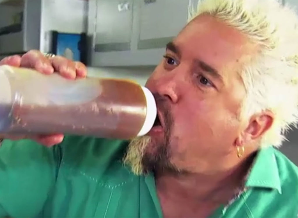 A screenshot from Diners Drive Ins and Dives from the Food Network where Fieri gulps some sort of mystery sauce.
