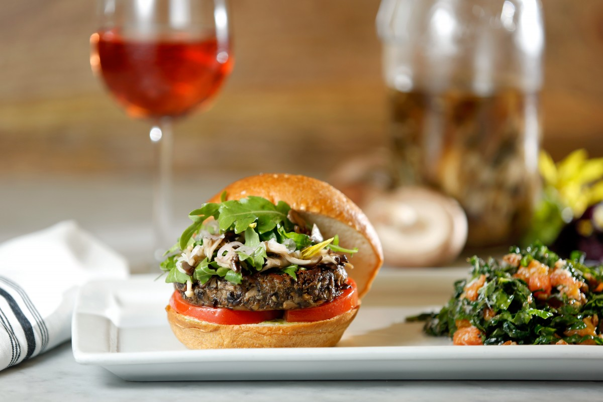Chef Domenica Catelli's Blended Burger (50-50 mix of house-ground beef and a blend of shiitake, cremini and dried porcini mushrooms, with arugula and pickled maitake and enoki mushrooms on top, served with Domenica's signature kale salad, at Catelli's restaurant in Geyserville (Alvin Jornada / The Press Democrat)