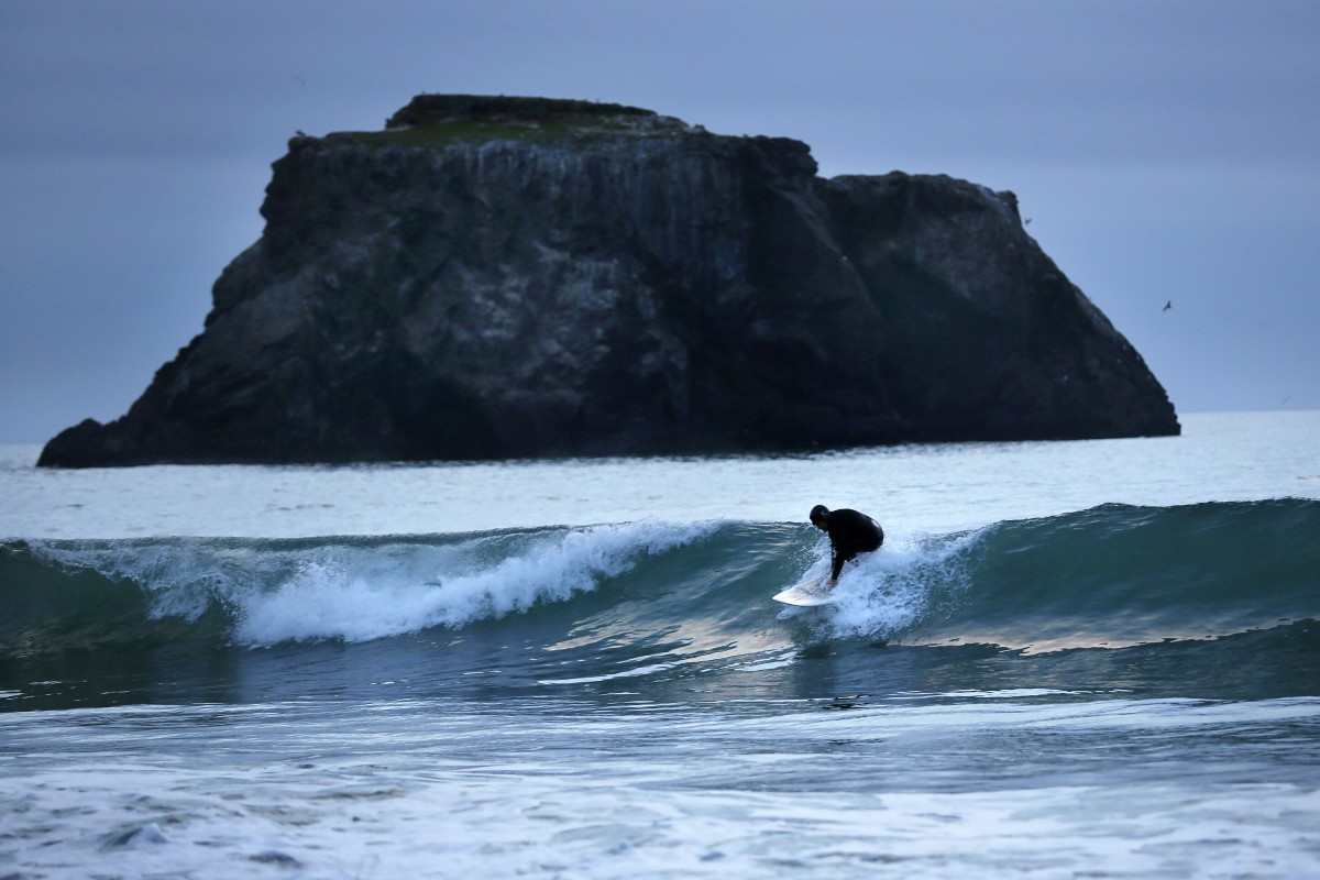 Eric Austensen tries to catch one last wave before the sun sets along Goat Rock State Beach on Tuesday, February 25, 2014. Austensen has been surfing the chilly waters along the Sonoma County Coast for over 30 years.(Conner Jay/The Press Democrat)