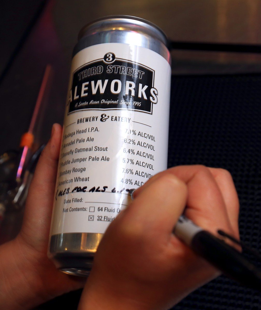 """Third Street Aleworks bartender Jordan Thome writes the name of the beer before filling a quart can """"Crowler"""" of their Ales for ALS IPA in Santa Rosa. (John Burgess / The Press Democrat)"""