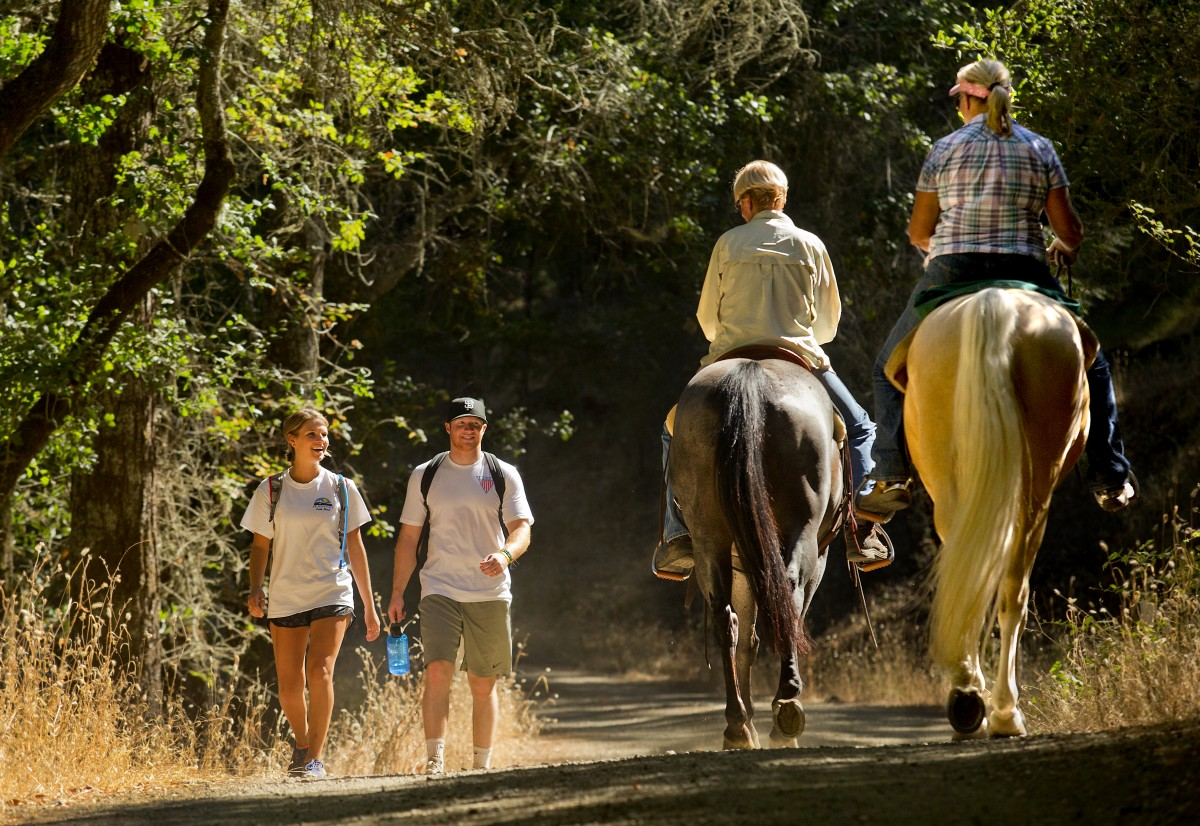 Hikers Mattie Johnson and Nate Kitchen of Santa Rosa share a smile and a hello with equestrians Katherine Lane and Tammi Bernd of Sonoma at the newly renamed Trione-Annadel State Park in Santa Rosa on Friday. Bernd has been riding horses on the land since 1968. (JOHN BURGESS/The Press Democrat)