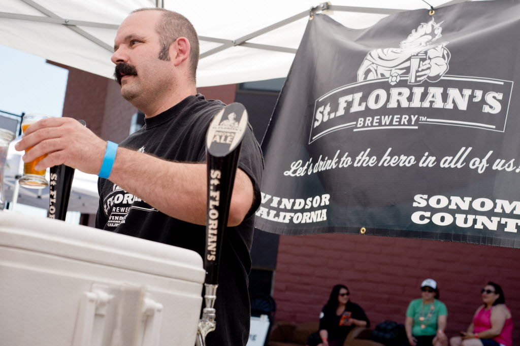 Aron Levin of St. Florian's Brewery pours beer for attendees of Sonoma County Beerfest in Santa Rosa. (Alvin Jornada / The Press Democrat)