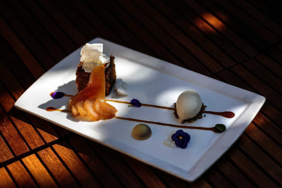 "Scott Noll's ""Milk & Honey"": honey-pickled poached pear against honey tea cake near dehydrated ""crunchy"" milk with honey ice cream sitting on bee pollen."