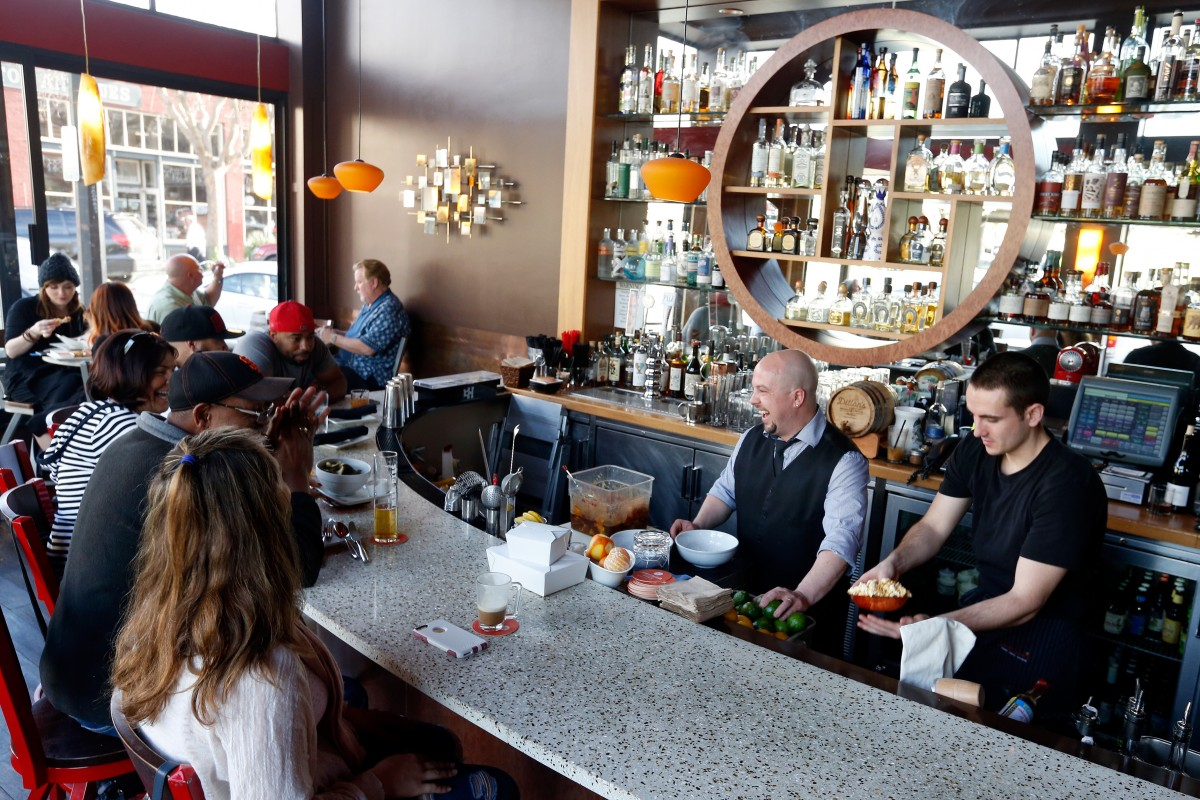 Bar manager Alex Kaplan, second from right, jokes with customers while preparing their drinks at Jackson's Bar and Oven in Santa Rosa, California on Tuesday, February 23, 2016. (Photo credit: Julie Grosse)