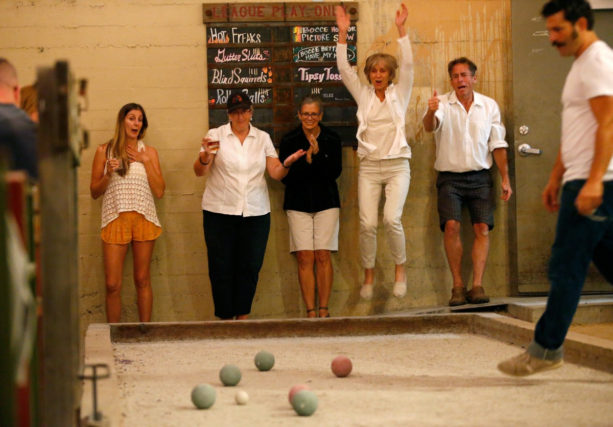 Bocce players react to a close call during bocce league play at Campo Fina restaurant in Healdsburg, California on Thursday, July 14, 2016. (Alvin Jornada / The Press Democrat)