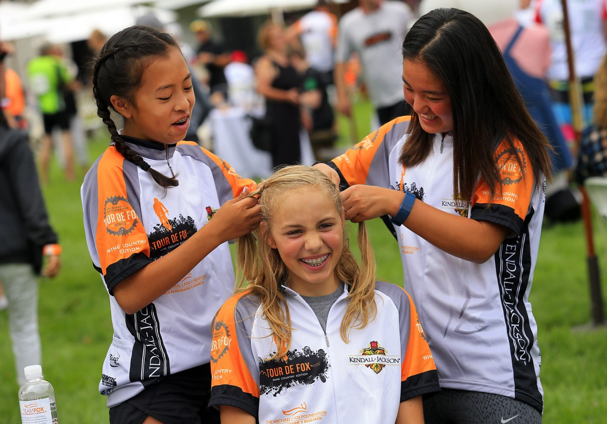 Julia Chow, left, and Noel Namba braid the hair of Madison Kiss at the after party for the Tour de Fox Wine Country Edition at the Kendall-Jackson Winery in Santa Rosa. (JOHN BURGESS/The Press Democrat)