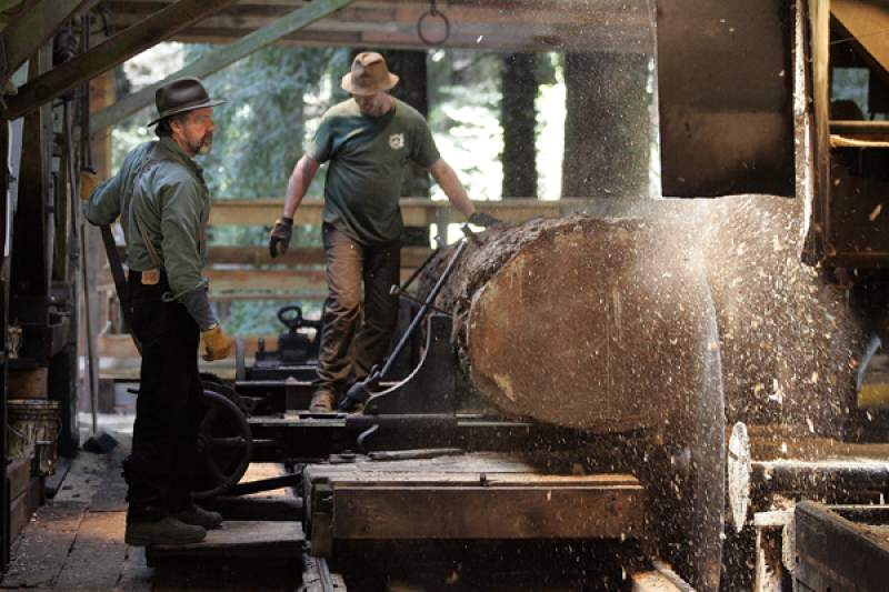 Harvey Henningsen, left, and Ron Sturgeon run a log through the blades of hte headrig at Sturgeon's Mill.