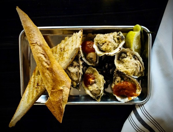Baked oysters (choice of classic chipotle BBQ, salsa verde, tasso herb) served with lemon & grilled baguette at the Shuckery in Petaluma. (Photo Courtesy: The Shuckery)