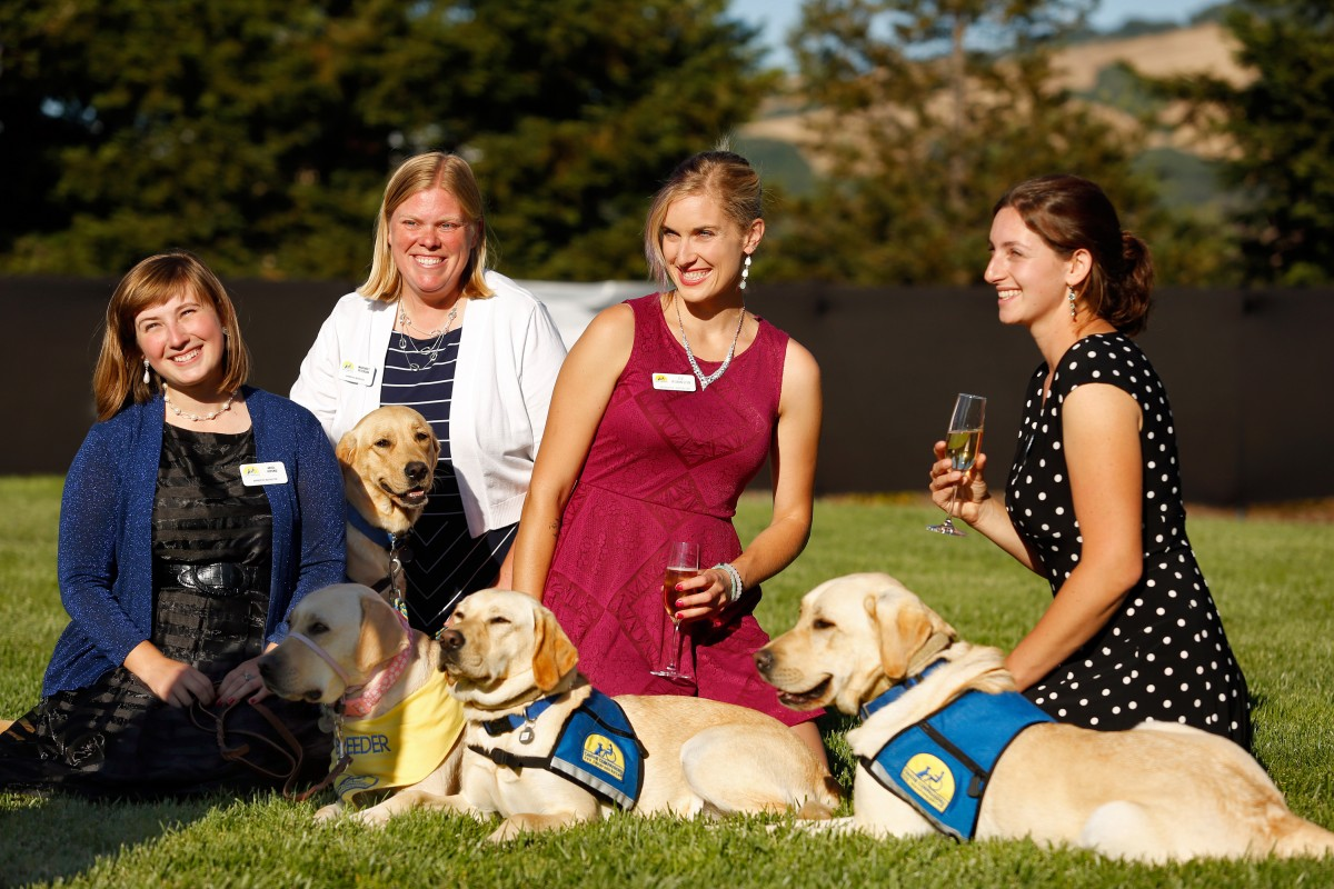 CCI apprentice instructors Ariel Vipond, left, Margaret Peterson, and Oz Robinson and CCI instructor Sarah Birman pose with a group of CCI dogs during the Sit Stay Sparkle gala Canine Companions for Independence in Santa Rosa.