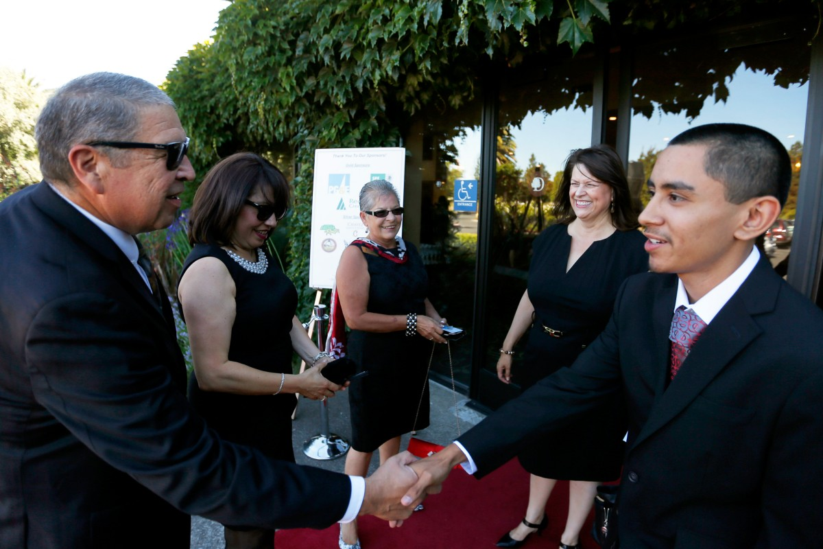 Ben Garcia, left, greets student Eric Maldonado while Carmen Garcia, second from left, Donna Zapata, and Carmen Cervantes look on during the Hispanic Chamber of Commerce Sonoma County's Dream Big Gala in Rohnert Park,
