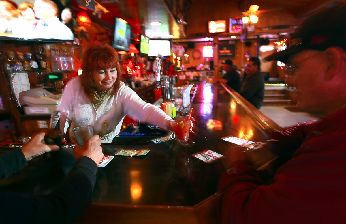 Bartender Dorothy Drew, a 30-yaar veteran of the bar and eatery serves up a regular customer on Wednesday. (JOHN BURGESS / The Press Democrat)